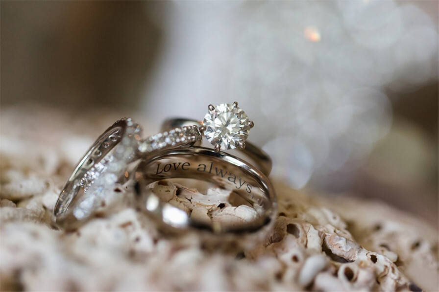 diamond wedding rings with engraving on beige background